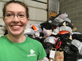Woman standing in front of large donation pile