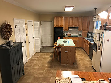 Outdated kitchen with storage cabient, island, and refridgerator