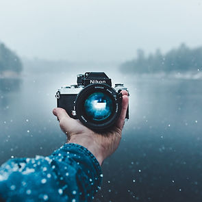 This is the image of a vlogging camera held by left hand and a scene of a river.