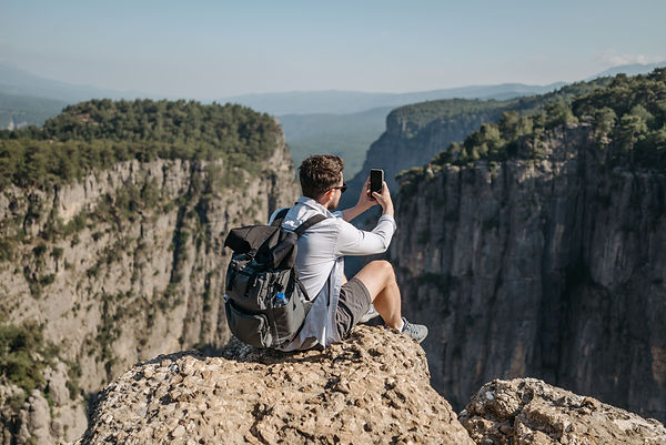 The image of an adventure vlogger shooting video on a hilltop.