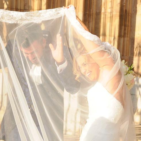 Novios tapados con el velo de la novia