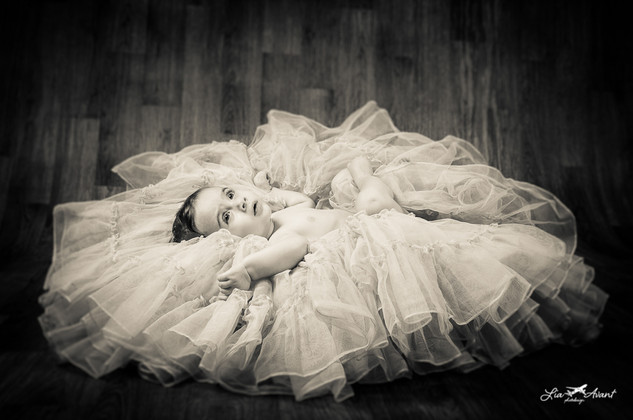 baby in pile of blankets, b/w