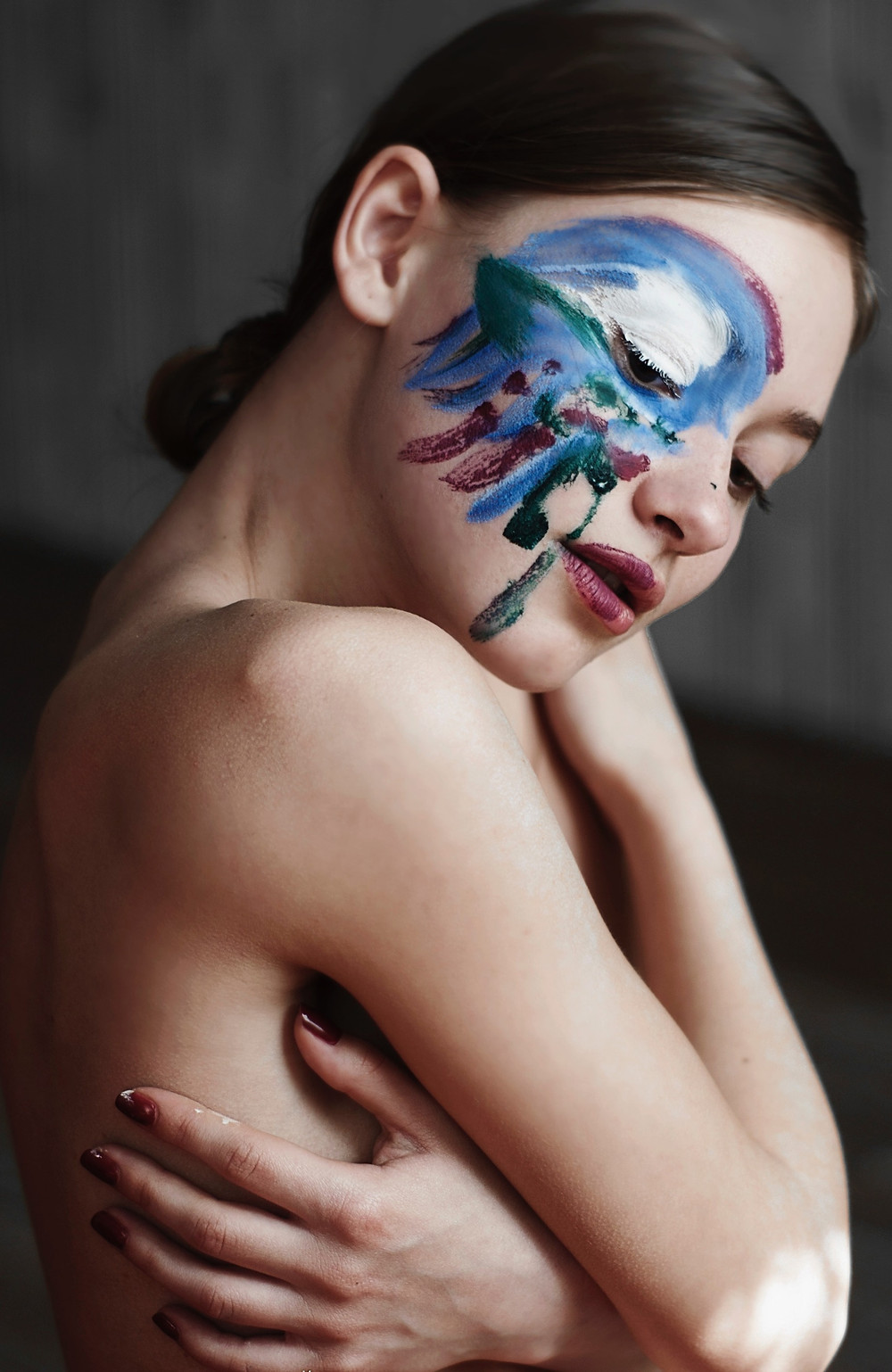 brunette woman with painted face hugging herself; by Svetlana Pochatun