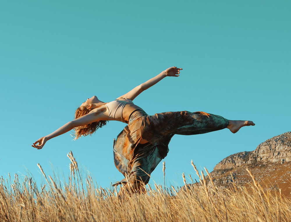 Caucasian woman dancing in a field; by Craig Chitima