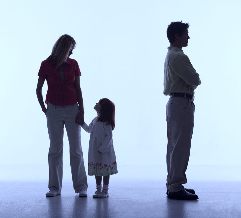 Caucasian family with the man standing apart from his wife and daughter.