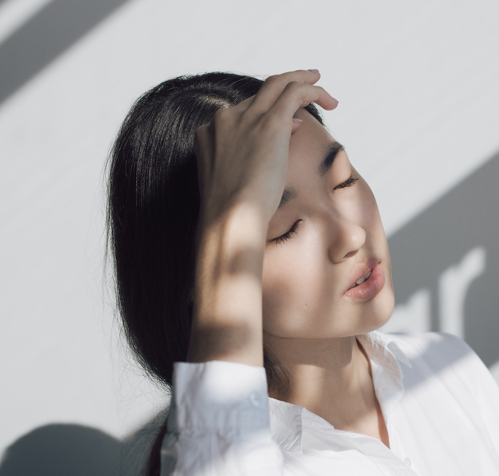 Asian woman closing her eyes; by Alony Haust
