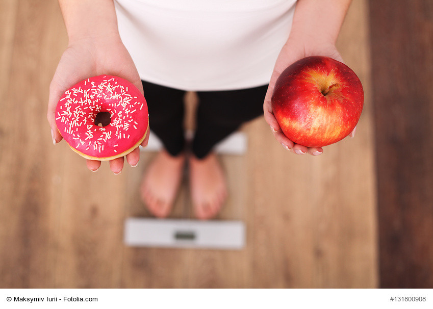 Woman weighing herself while holding Apple and doughnut