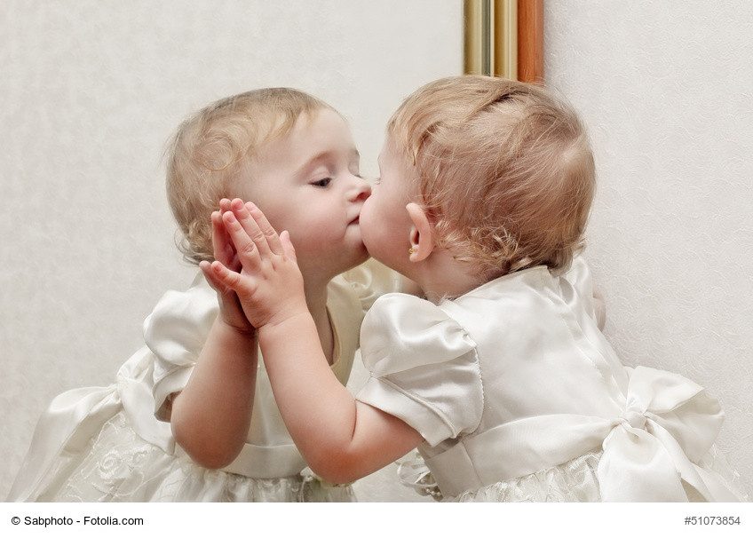 baby kissing her reflection in the mirror
