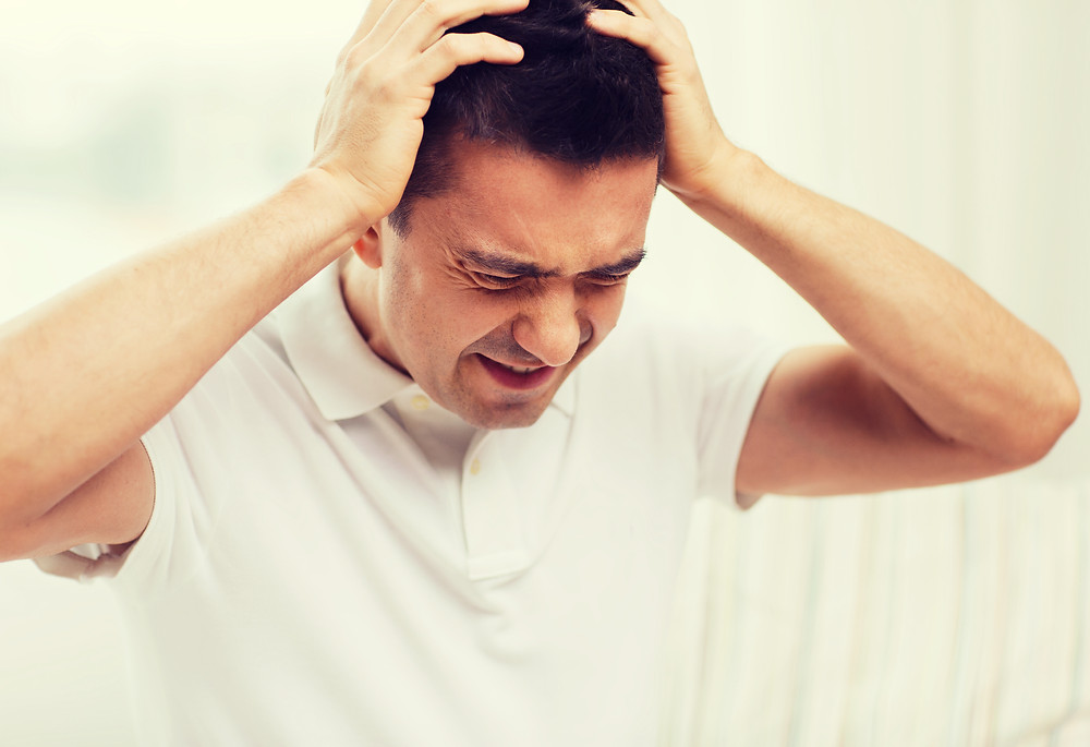 man holding head in frustration