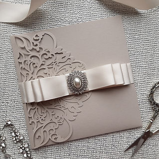 Lasercut pocketfold invitation with stunning embellishment and ribbon