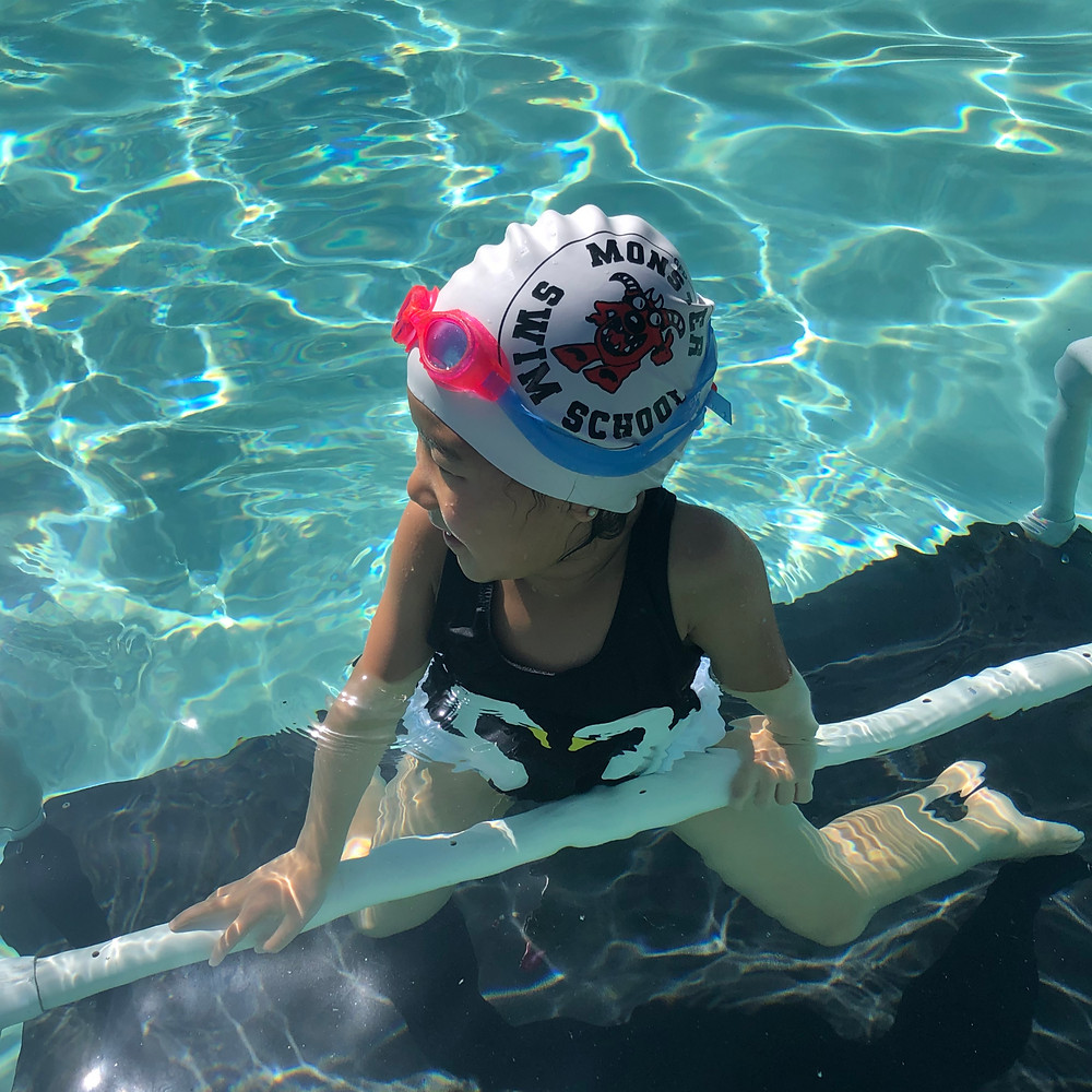 Girl in pool looking to the left and wearing a black swimsuit, a Monster Swim School swim cap, and pink and blue goggles.