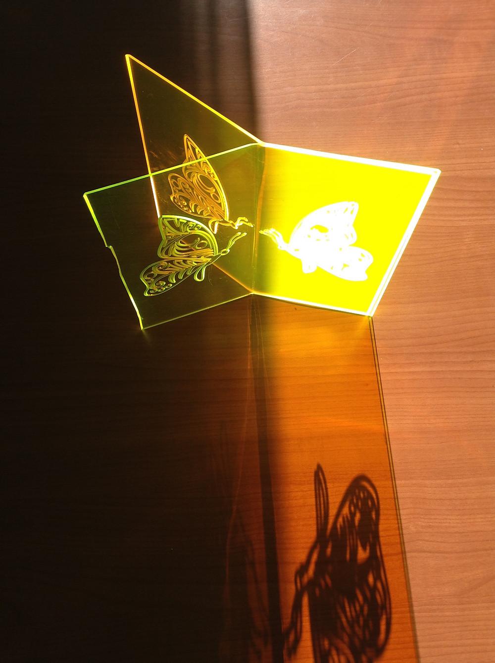 """Due pannelli """"light to light"""" curvati e poggiati su un tavolo, illuminati da un raggio di Sole. L'installazione artistica mostra che i pannelli """"light to light"""" possono essere anche composti fra loro e possono essere poggiati su superfici piani per varie applicazioni."""
