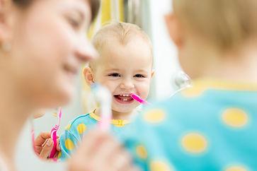 mother teaches baby brushing teeth.jpg