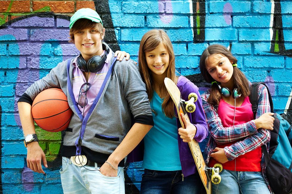 Row of happy teens by painted wall looki