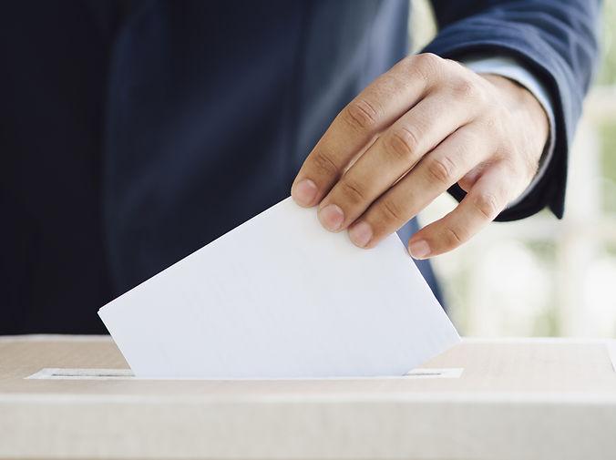 Man putting an empty ballot in election box.jpg