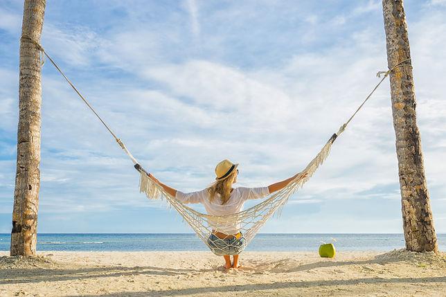 Woman in hat sitting in hammock on the b