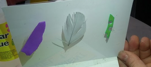 white postcard. three pieces of 'rubbish' glued on: L to R: purple foam, small white feather and green foam piece.