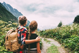 Hikers with backpack looking at mountain