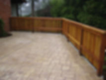 stamped concrete patio with a custom redwood fence
