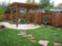 back yard landscape with a redwood arbor, pond and waterfall, flagstone stepstones across the lawn with a stamped concrete patio and decorative rock, landscape lighting and plants