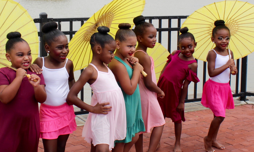 Seven Mini-Co Dancers pose in colorful dresses with yellow parasols.
