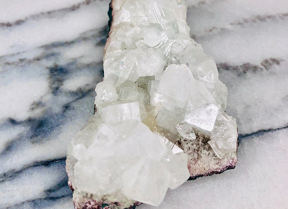 image of white apophyllite crystal specimen sitting on white marble background