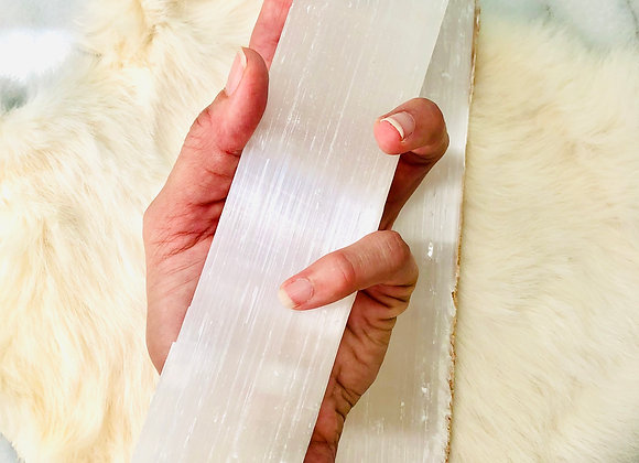 image of large selenite wand crystal specimens displayed in hand over white background