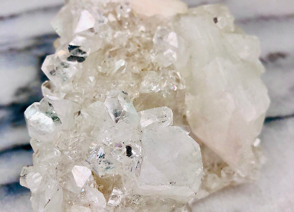 image of white apophyllite crystal specimen sitting on white marble background
