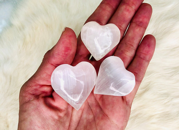image of small selenite heart crystal specimens displayed in hand over white background