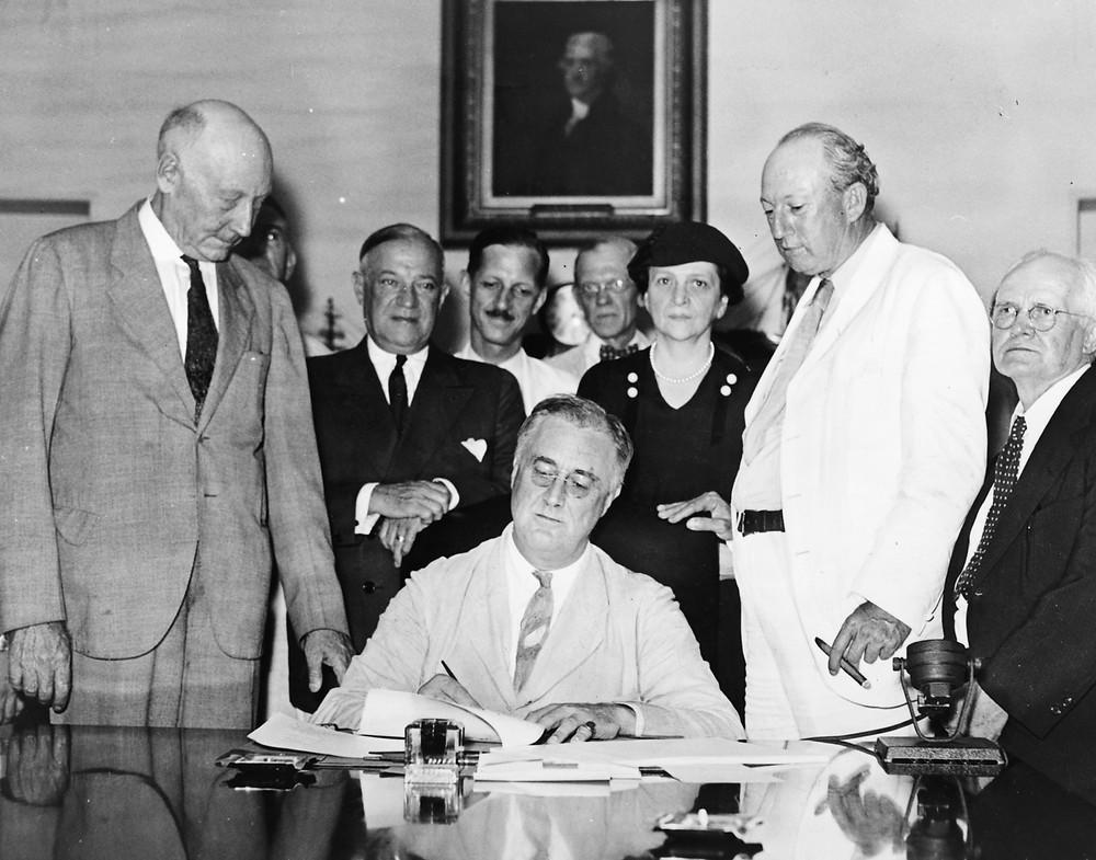 FDR signs the Social Security Act into law. (1935)