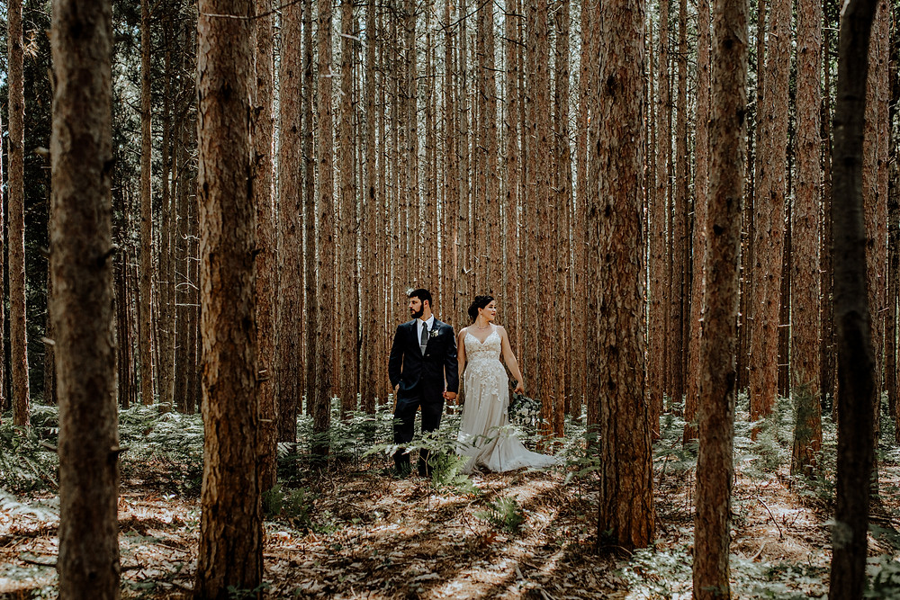 bride and groom wedding photo in the woods taken in manistee, michigan by little blue bird photography.