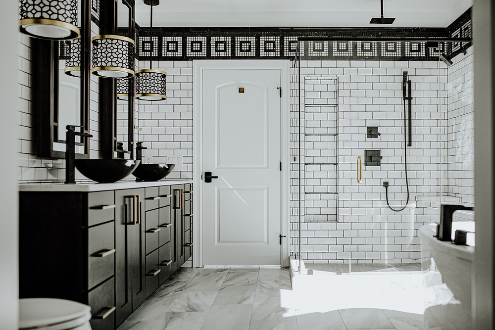 modern black and white bathroom remodel with a marble grecian tile border, subway tile, black vanity and brass hardware. Construction done by Michigan Valley Homes in Brooklyn, MI.Michigan.