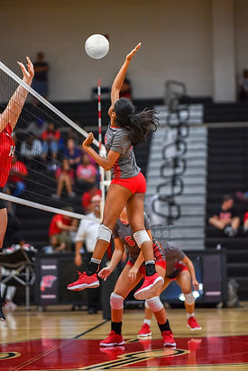 Girl volleyball player spiking the ball