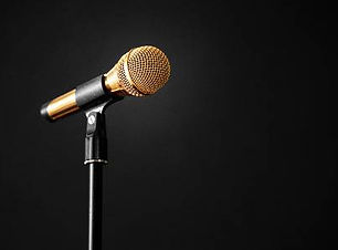 125060377-gold-microphone-on-stage-on-a-