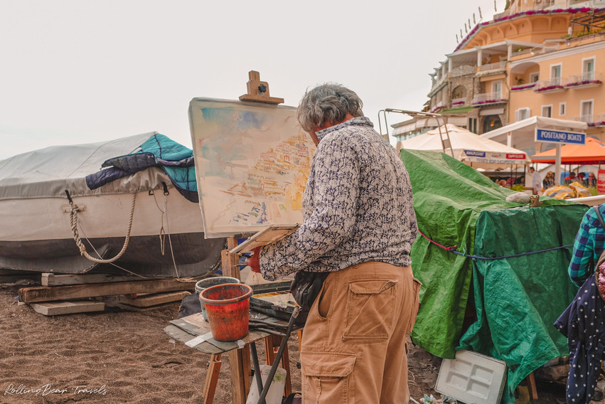 An artist painting on an easel by the beach of Positano | RollingBear Travels.