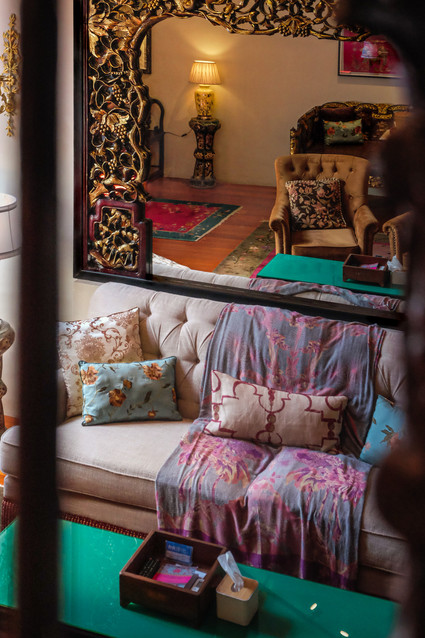 The Seven Terraces Stewart Apartment room interiors: Sofa with oriental cushions and antique Peranakan furniture / RollingBear Travels interiors photography.