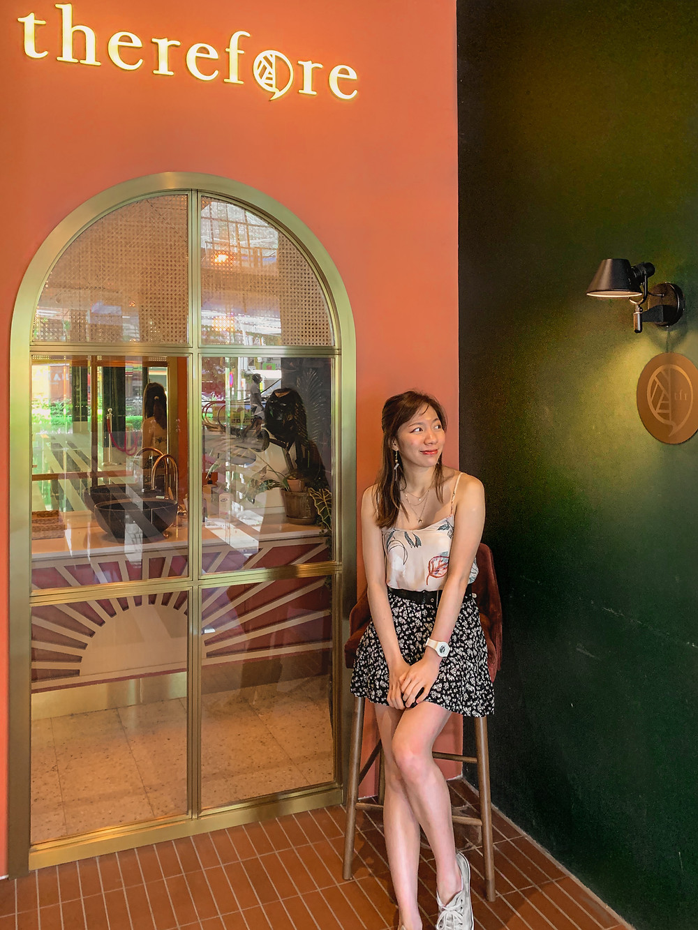 Style blogger in floral camisole and skirt outfit against entrance of Therefore Cafe, Malaysia, RollingBear Travels blog.