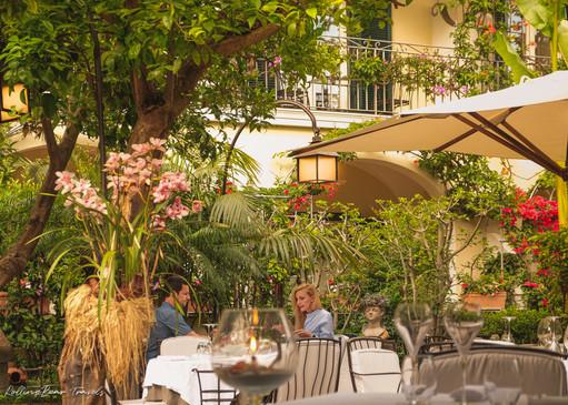 A couple dining al-fresco in the lush garden of al Palazzo restaurant. | RollingBear Travels