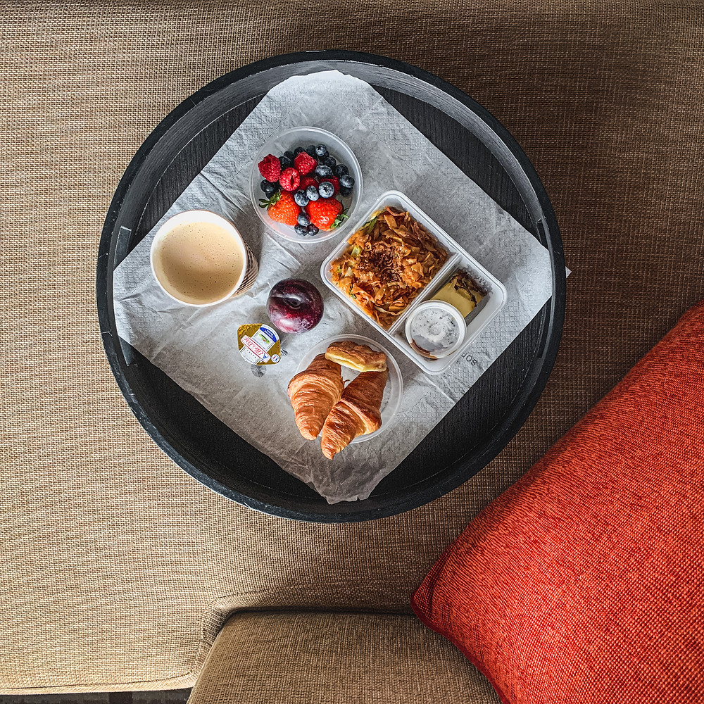 Rollingbear Travels blog/ contrasty flat lay of breakfast spread, brown fabric sofa, bright orange cushion