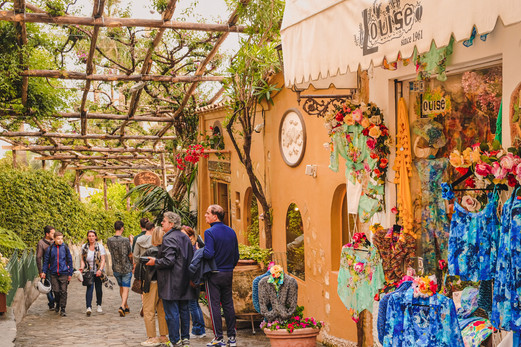 Orange wall, colourful clothes displays, cobbled street and tourists at Positano, Italy | travel photography by RollingBear Travels.