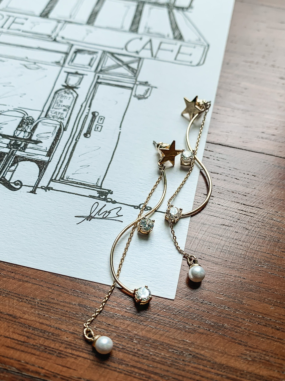Joli Moon gold star and pearl drop earrings atop ink illustration of a cafe.