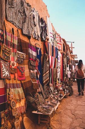 Ait-Ben-Haddou: Girl walks beside a display of Moroccan handicrafts | RollingBear Travels.