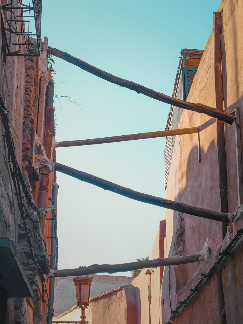 Medina street photography: timber beams between adobe buildings | RollingBear Travels