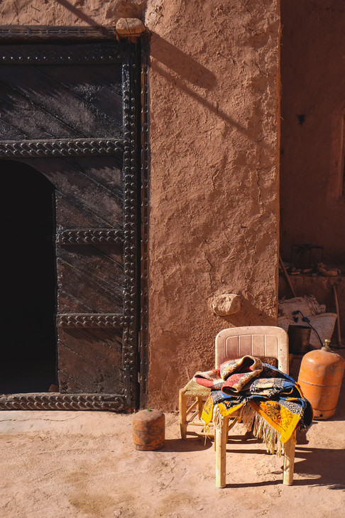 Ait-Ben-Haddou: Plastic chair against adobe wall and antique metal doors | RollingBear Travels.