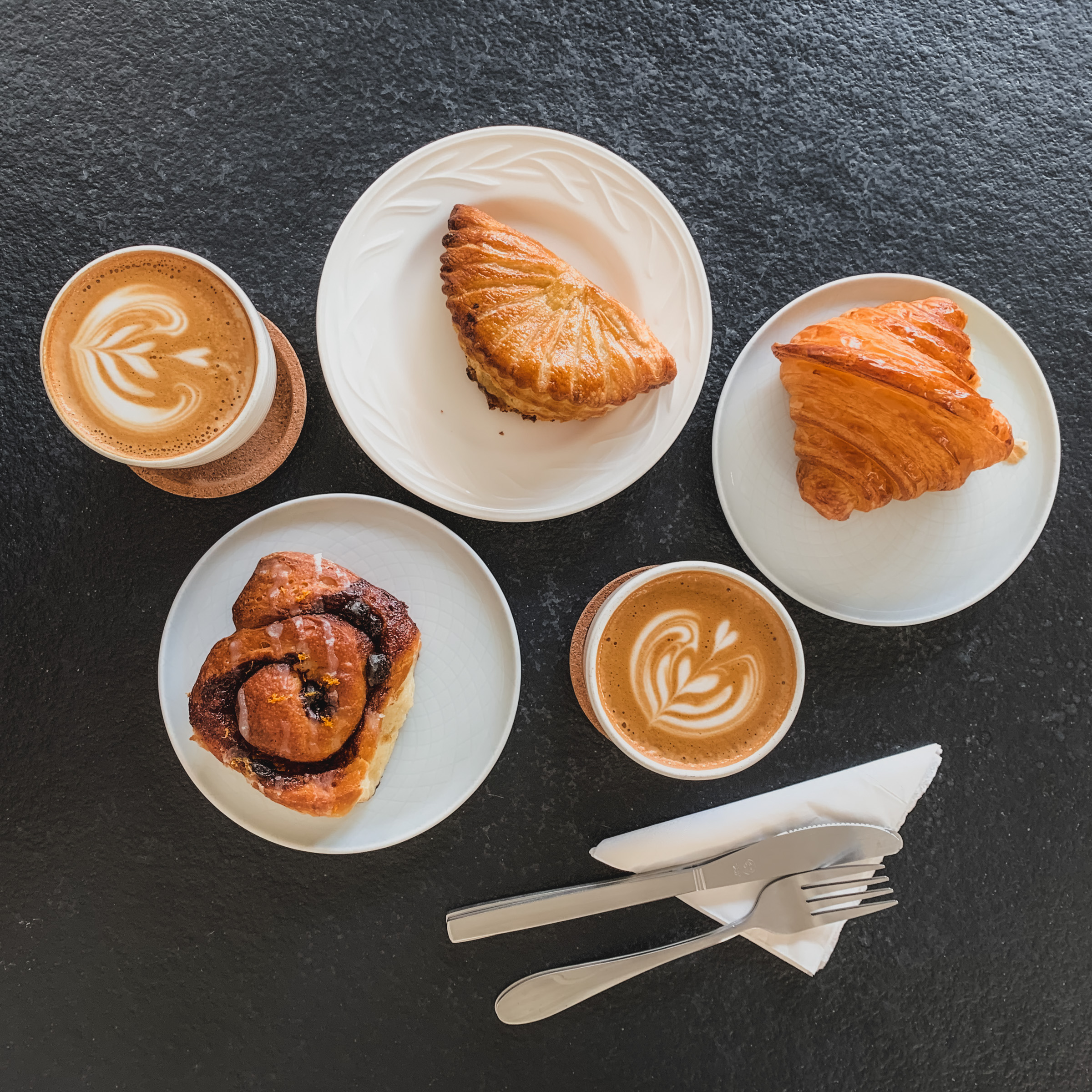 Lifestyle photography : Latte, pastries, cinnamon roll spread, RollingBear Travels blog.