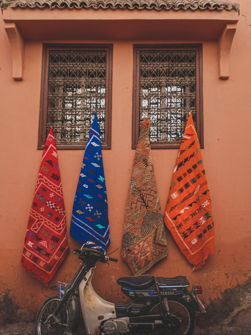 Colourful Moroccan patterned fabrics and a motorcycle in front of an adobe building | RollingBear Travels