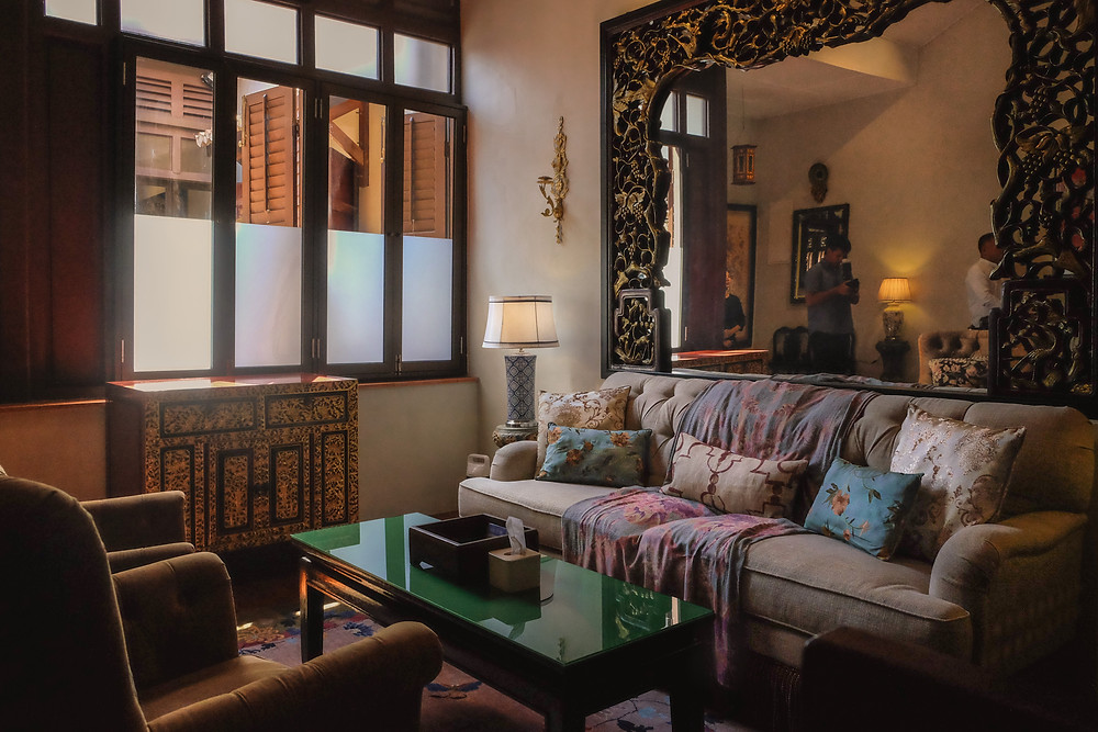 The Seven Terraces Stewart Apartment room interiors: Sofa with oriental cushions and antique Peranakan furniture / RollingBear Travels photography.