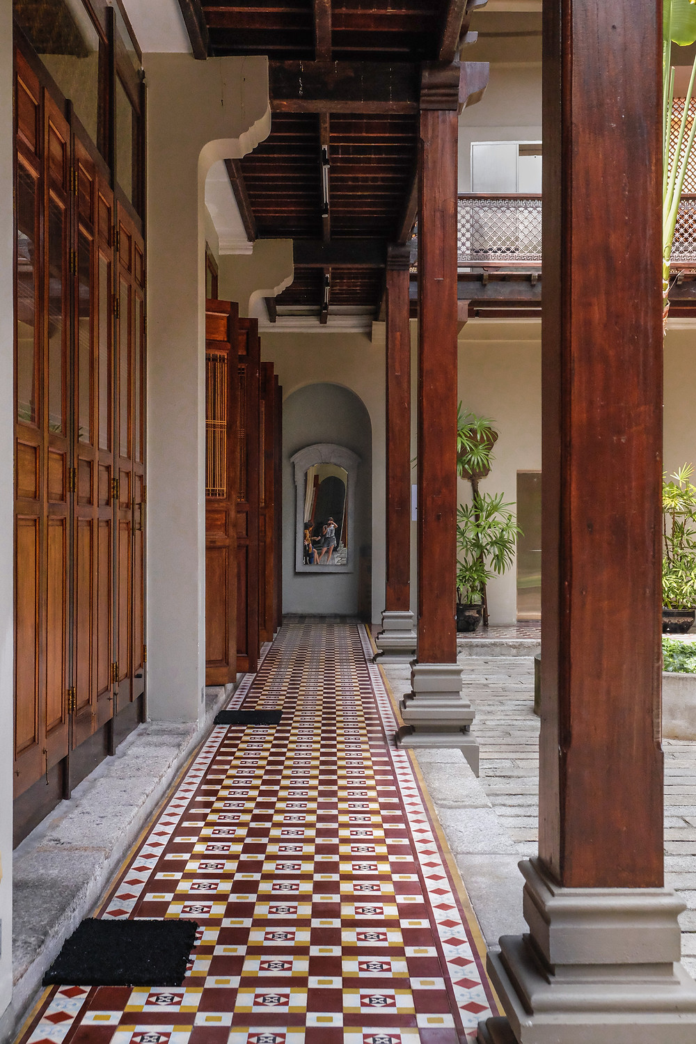 Seven Terraces Hotel courtyard walkway with Peranakan timber doors and colourful tiles, photography by RollingBear Travels.