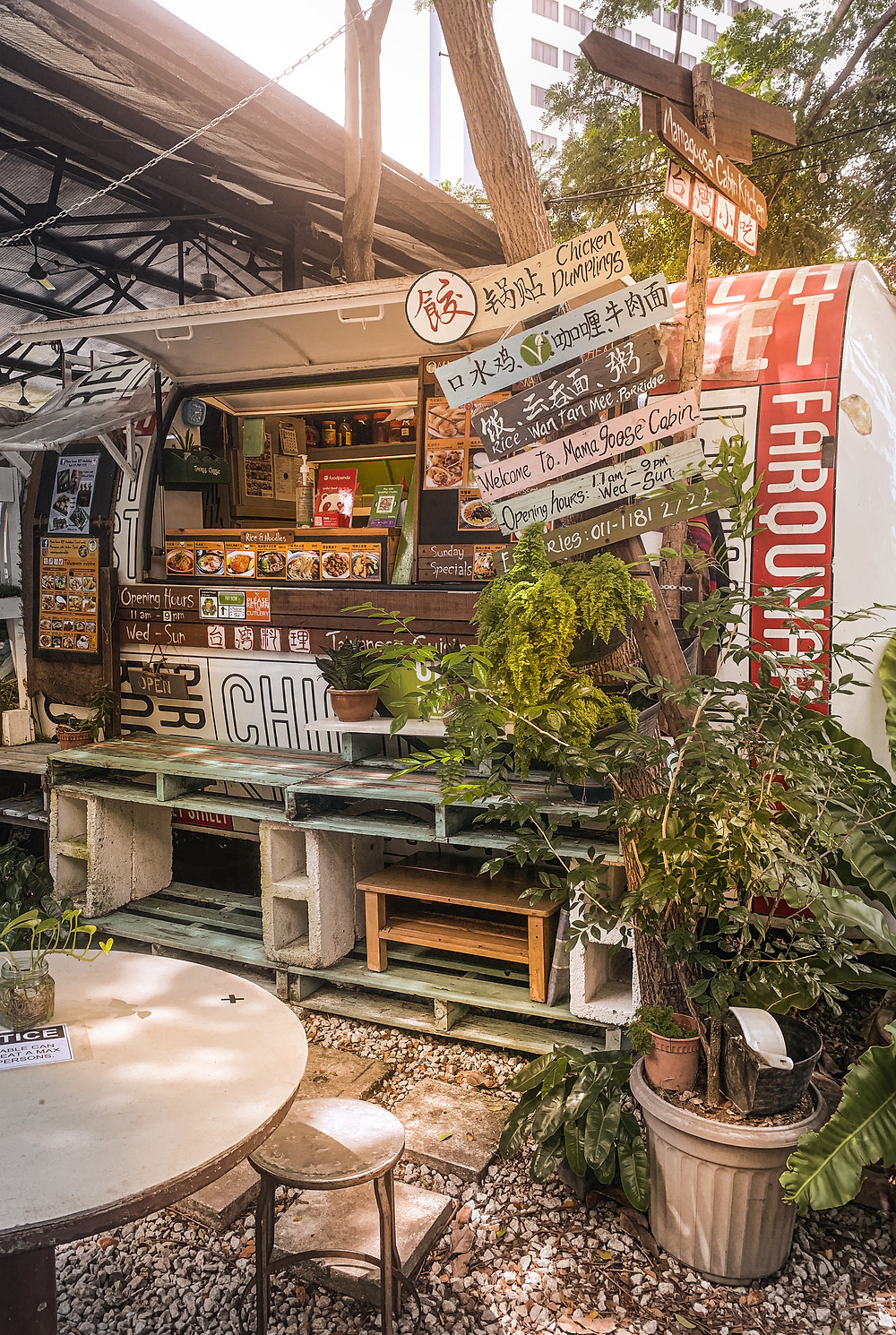 Rustic wooden menu signs, outdoor seating, cabin kitchen facade of Mama Goose Cabin, Hin Bus Depot, RollingBear Travels blog.