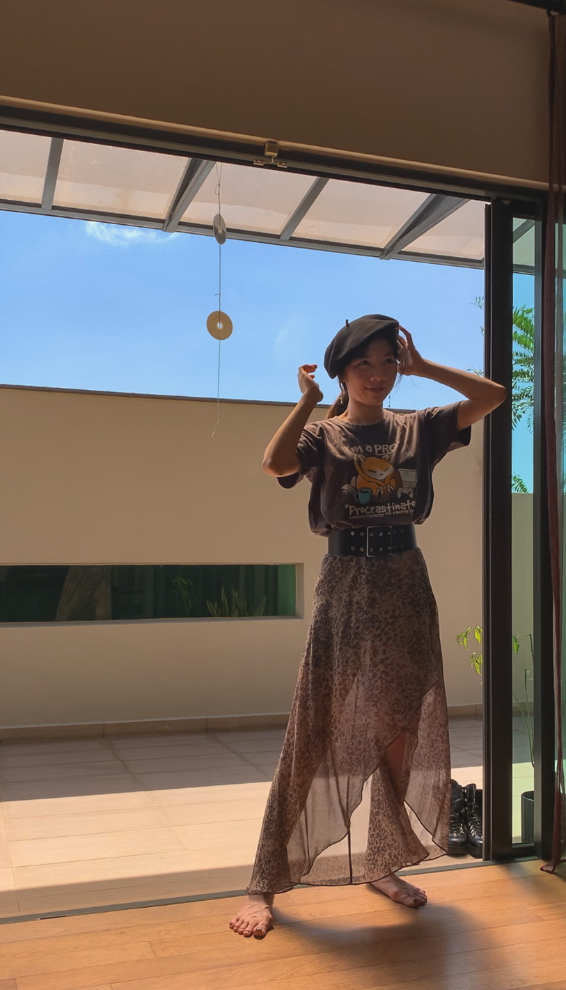 Blogger in a t-shirt and maxi skirt adjusts a black beret.
